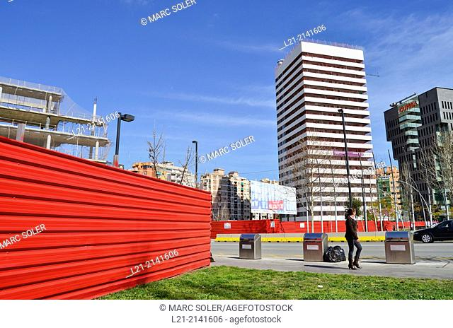 Recycling containers, green grass, red wall, buildings, blue sky. Plaça Europa, Plaza Europa, District VII, Gran Via, Hospitalet de Llobregat