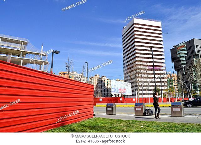 Recycling containers, green grass, red wall, buildings, blue sky. Plaça Europa, Plaza Europa, District VII, Gran Via, Hospitalet de Llobregat