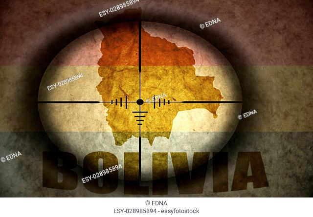 sniper scope aimed at the vintage bolivian flag and map