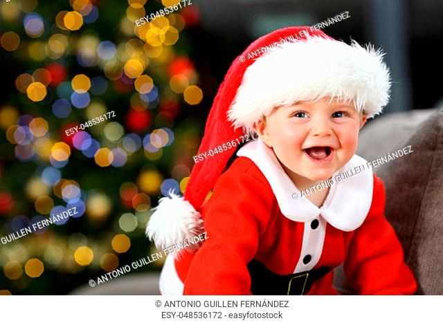Baby laughing wearing santa disguise in christmas