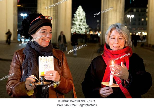 Two participants in the chain of lights standing at the Brandenburg Gate in Berlin, Germany, 19 December 2015. A man from Baden-Wuerttemberg called for the...