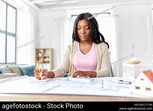 female architect with house model and blueprint
