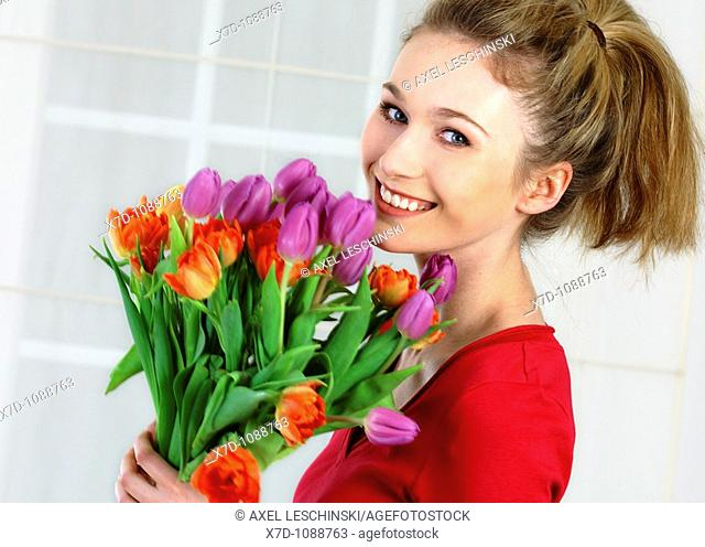 portrait of young woman holding bunch of tulips in hands
