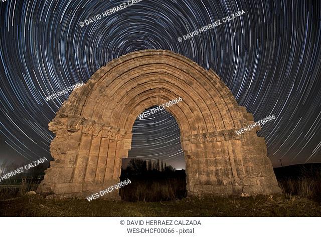 Spain, Sasamon, Arco de San Miguel de Mazarreros with star trails in the background