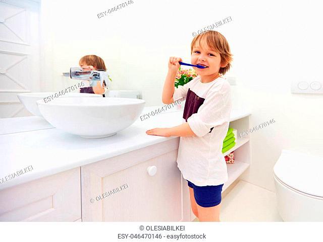 happy young boy brushing teeth in bathroom
