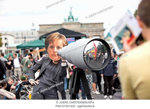 """A woman holding a mock telescope and wearing a mask showing German Chancellor Merkel attends the demonstration """"""""Liberty instead of Fear"""""""" in Berlin, Germany"""