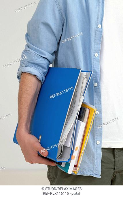 Teenager carrying files and folders