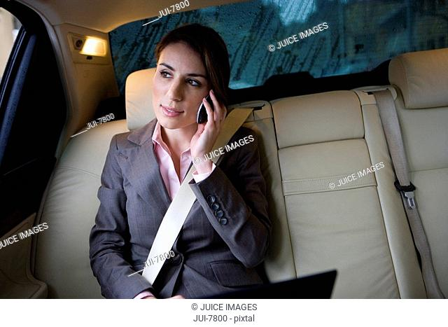 Businesswoman sitting in backseat of car, wearing seatbelt, using mobile phone and laptop, front view tilt