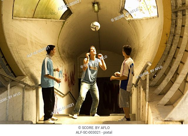 Teenage boys heading ball in tunnel