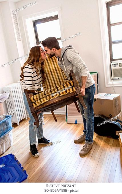 Moving house: Young couple lifting chair, rubbing noses over chair