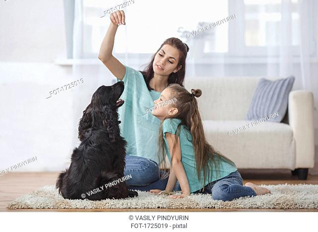 Mother and daughter playing with dog in living room at home
