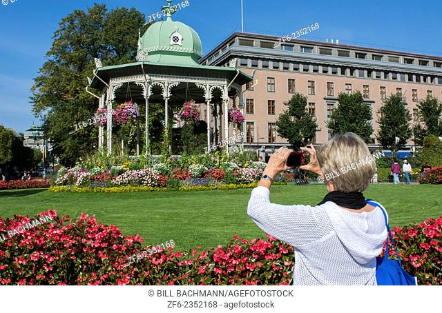 Bergen Norway music Pavillion colorful gazebo with flowers with woman tourist taking cell phone photo in downtown
