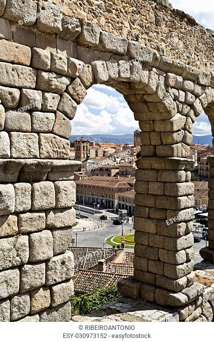 View of the old town through an arch of the roman aqueduct in Segovia, Spain