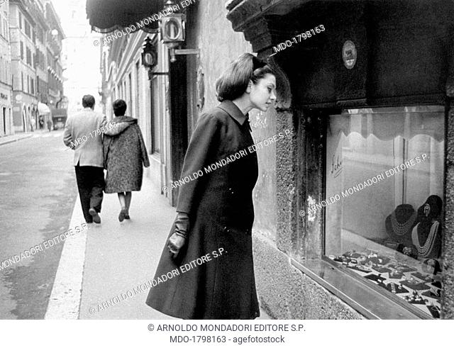 A woman looking at a jeweller's shop window in Via Condotti. Rome (Italy), 1962