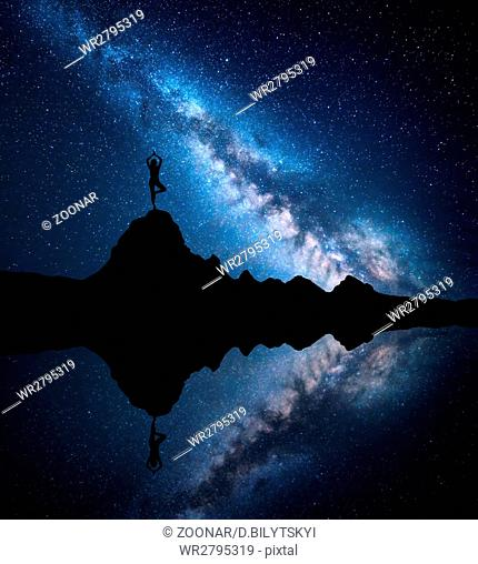 Milky Way with silhouette of a standing woman practicing yoga
