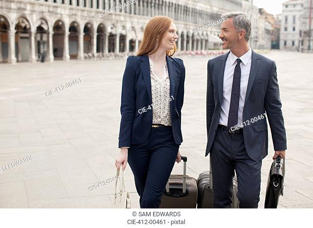 Smiling businessman and businesswoman pulling suitcases through St. Mark's Square in Venice