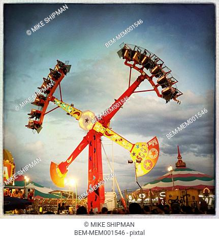 Illuminated amusement park ride under cloudy sky