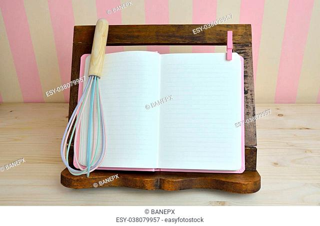 Blank cook book and egg whisk on wooden book holder with pink-yellow background