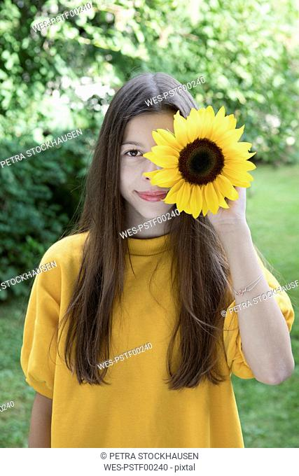 Portrait of smiling girl with sunflower in the garden