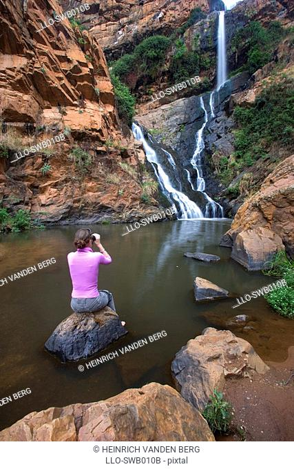 Woman Sitting on Rock Looking at Waterfall  Witwatersrand Botanical Gardens, Gauteng Province, South Africa