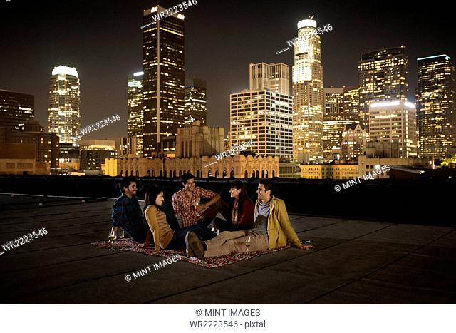 A group of friends gathered on a rooftop overlooking a city lit up at night