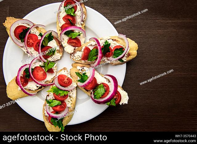 bruschetta with tomatoes, cheese, onions and parsley