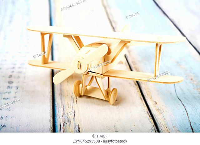 Wooden airplane model isolated on white wooden background