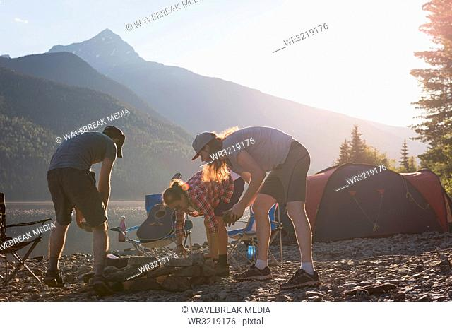 Group of hikers making preparation for campfire