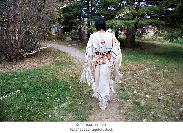 Native American woman walking outside wearing a traditional dress; Rossburn, Manitoba, Canada