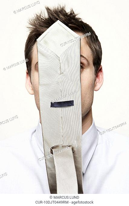 Young business man with tie having stuck to his face
