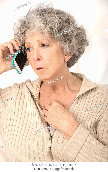 Puzzled beautiful senior woman on the phone at home looking worried
