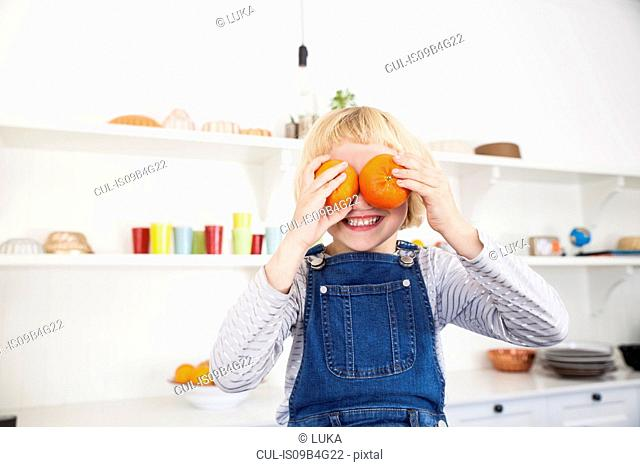 Portrait of cute girl in kitchen holding oranges to her eyes