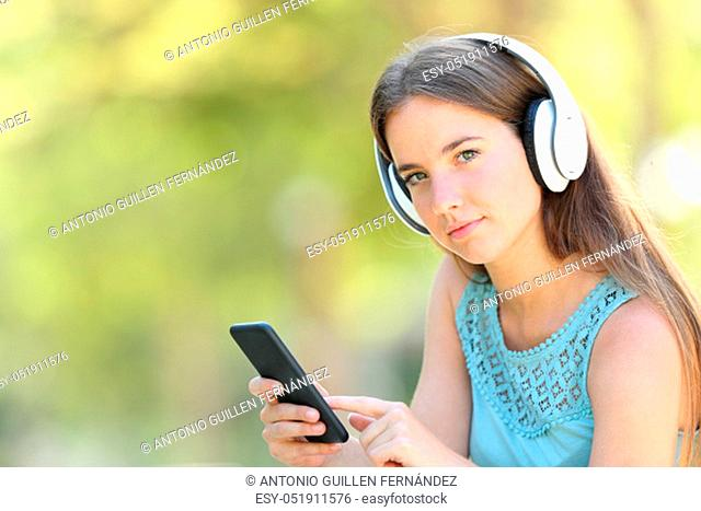 Serious woman listening to music holding smart phone looking at camera in a park with a green background