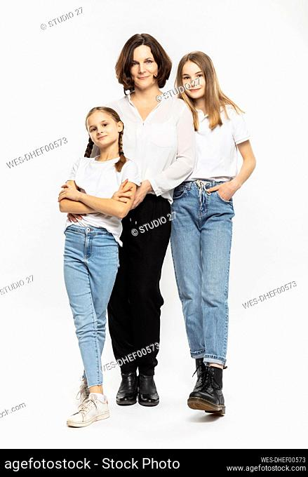Mother and daughters standing together against white background