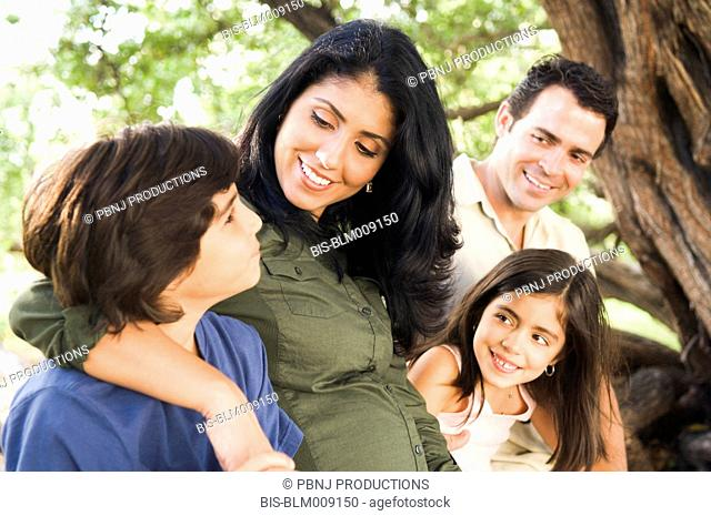 Mixed race family sitting on large tree branch