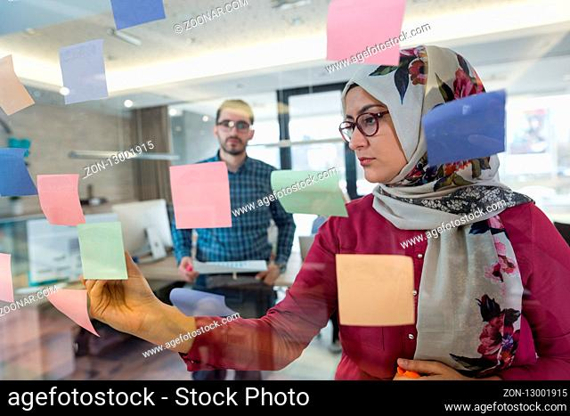 Beautiful Arab woman wearing hijab putting sticky notes on glass in modern office