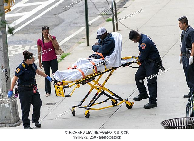 FDNY Emergency Service Technicians assist a homeless individual sleeping on the sidewalk in the Chelsea neighborhood of New York