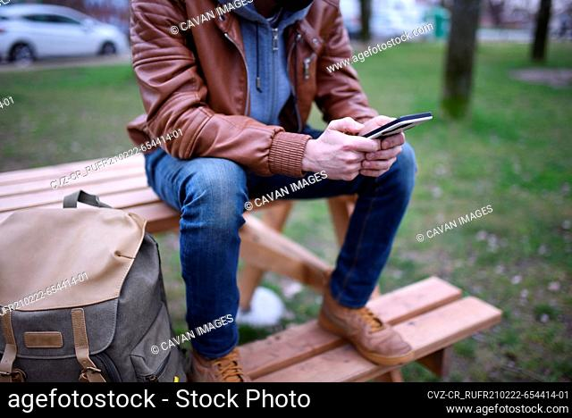 Image focused on the hands of a man with his mobile phone on a wooden bench in an open space