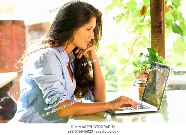 Side portrait of beautiful woman sitting at cafe using laptop