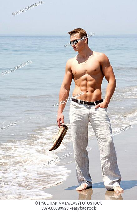 Toned cute handsome male standing on the beach with naked torso showing six pack abs holding shoes in hand wearing sunglasses and hand in pocket