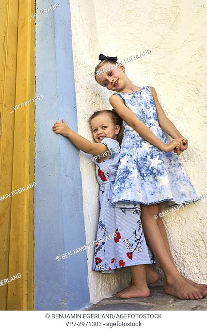 two candid siblings enjoying togetherness next to house door. Australian ethnicity