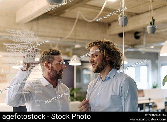 Two businessmen working on a project in office