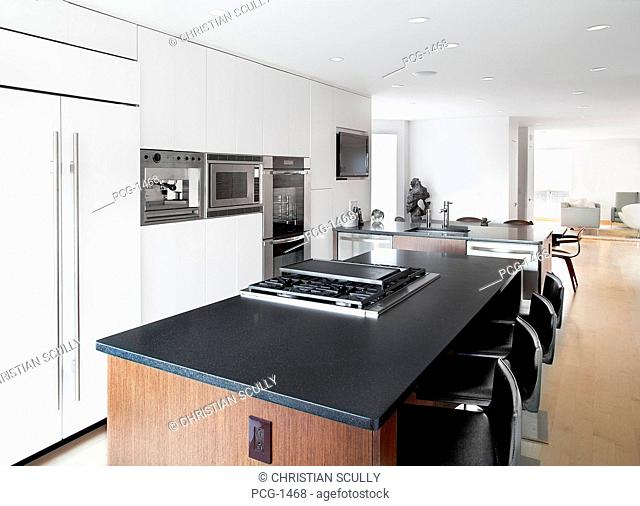 A house interior, a fitted kitchen with an island unit. Black countertop, modern appliances with swivel stools, a television monitor, refrigerator