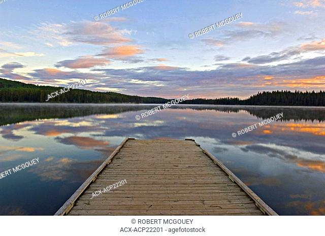A early morning summer sunrise from the boat dock on Jarvis Lake in William A Switzer Provincial Park Alberta Canada