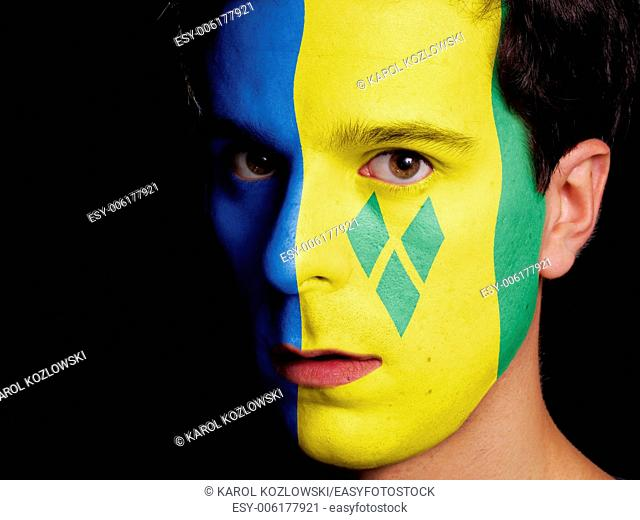 Flag of Saint Vincent and the Grenadines Painted on a Face of a Young Man