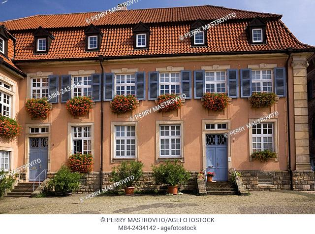 White with gray trim windows on old architectural style building decorated with flower boxes of red geraniums, Speyer, Germany