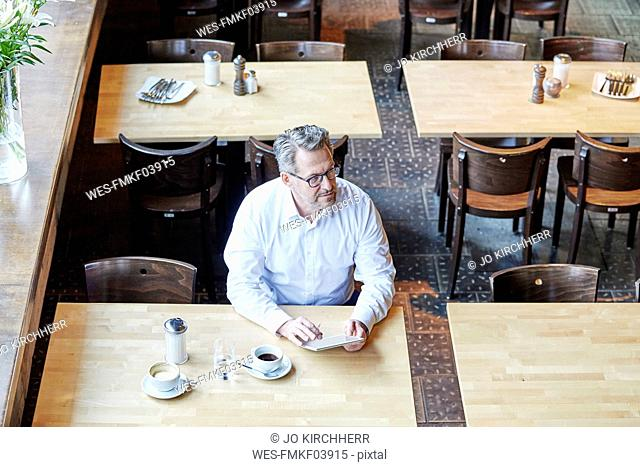 Mature businessman in cafe using tablet