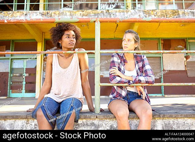 Young female friends sitting near railings outdoors