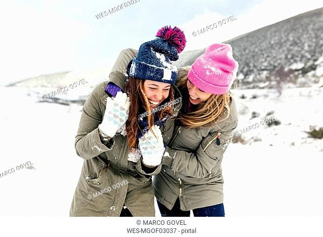 Two friends having fun in the snow