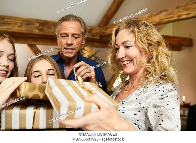 Parents and daughters with presents in front of Christmas tree, portrait